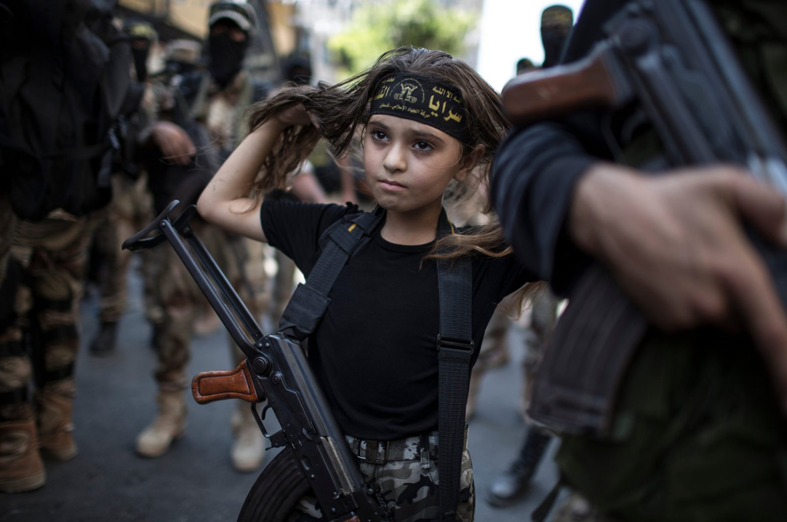 A Palestinian girl with a Kalashnikov rifle, amid Islamic Jihad militants in Gaza City Human Diversity