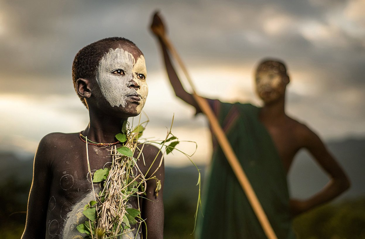 A boy of the nomadic Suri tribe of Ethiopia, in traditional face-body paint and attire Human Diversity