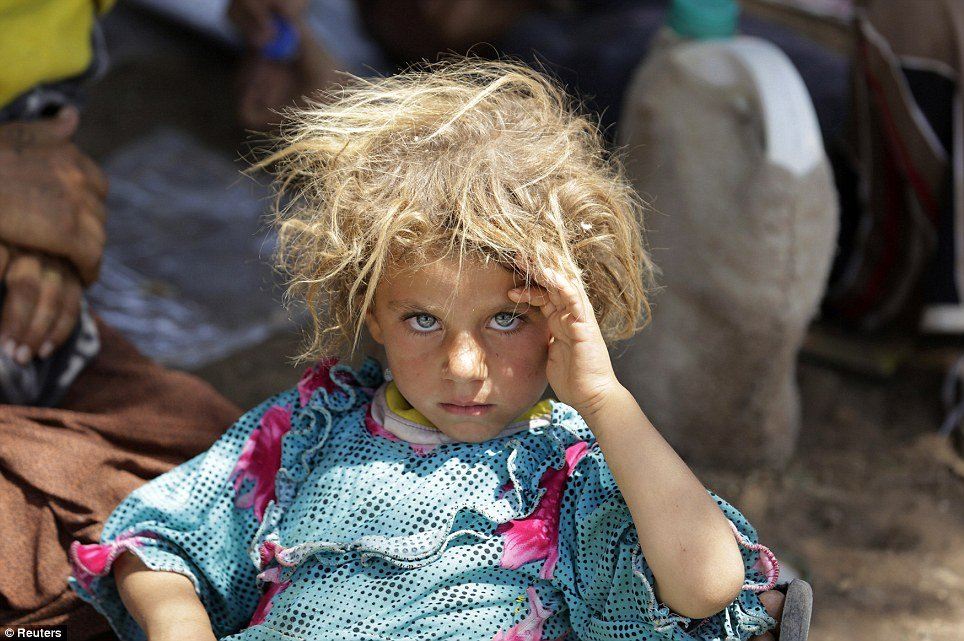A girl from the minority Yazidi sect rests at the Iraqi-Syrian border crossing in Fishkhabour, Dohuk province after fleeing Isla Human Diversity