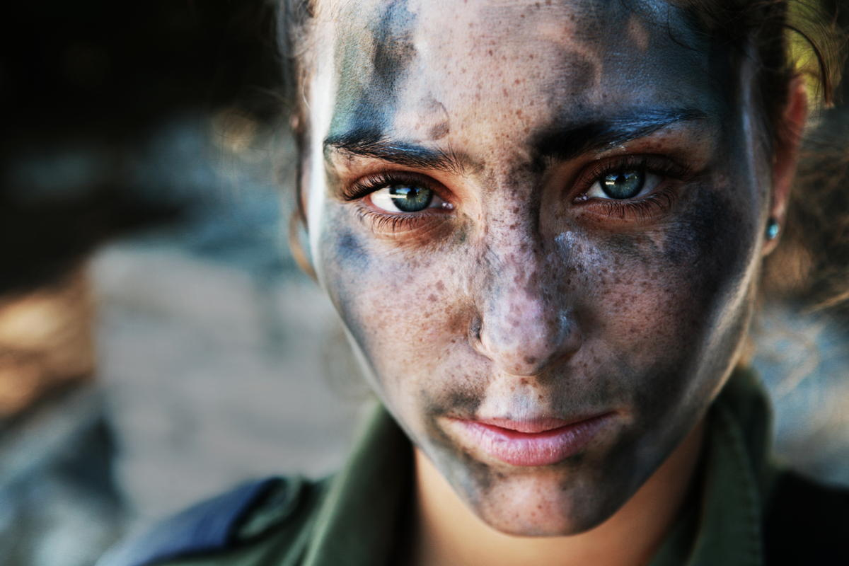 An 18 year old IDF soldier pauses after a long run in full gear and battle paint. Human Diversity