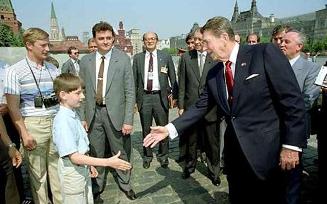 Vladimir Putin (far left) as a young KGB spy, meeting Ronald Reagan. Young Celebrity