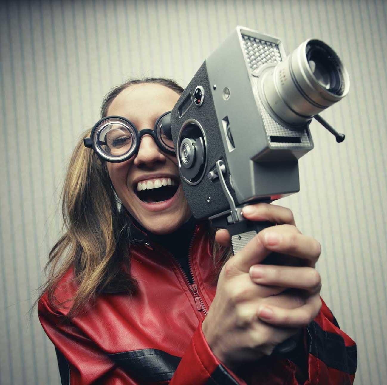 Nerdy woman using old fashioned cine camera